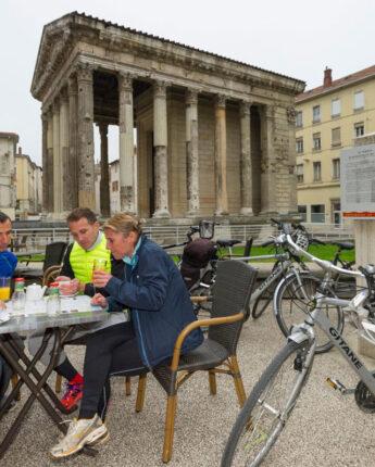 Personnes buvant un café avec leur vélo devant le Temple d'Auguste et de Livie
